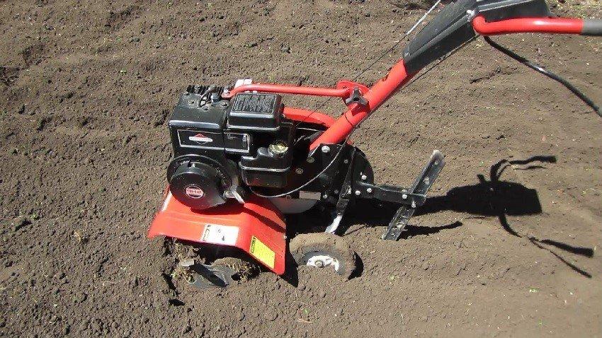легкий мотоблок обрабатывает землю